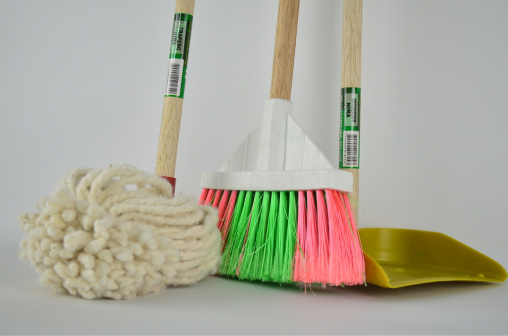 How to become a cleaner person: Picture of the bottoms of a mop, broom, and dustpan.