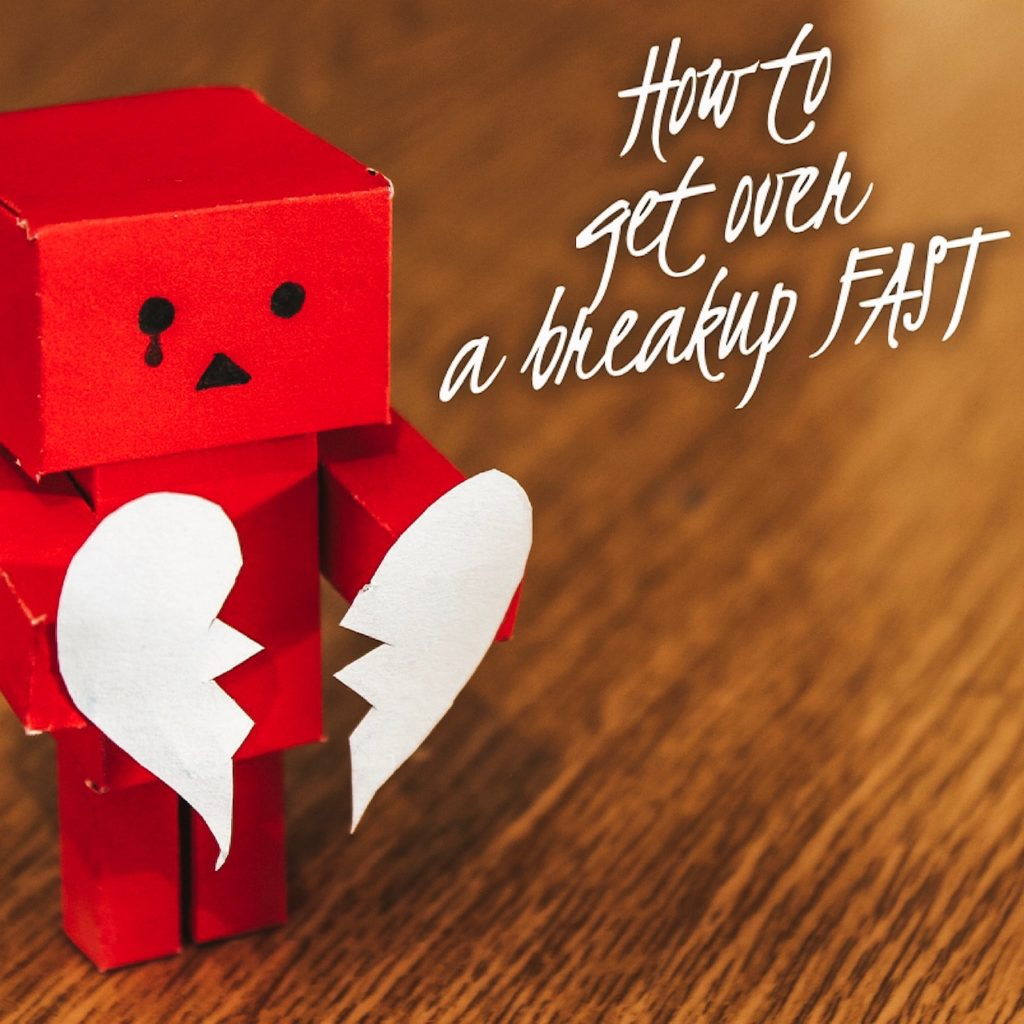 "A little block-shaped robot made of paper holding a broken heart, also made of paper. Words next to it read ""How to get over a breakup FAST."""