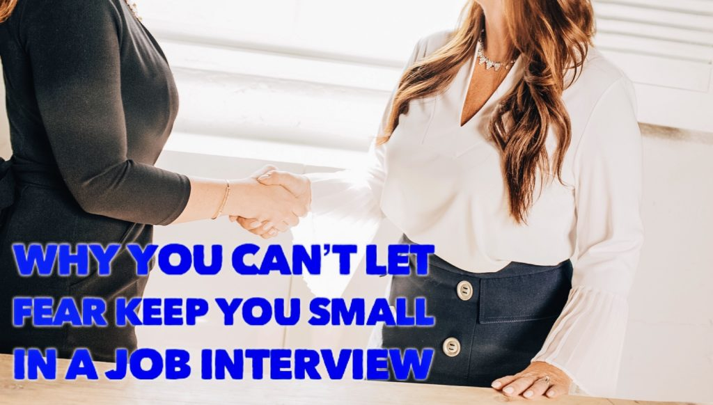 "Two women shake hands with the text ""Why You Can't Let Fear Keep You Small in a Job Interview"" displayed over them."